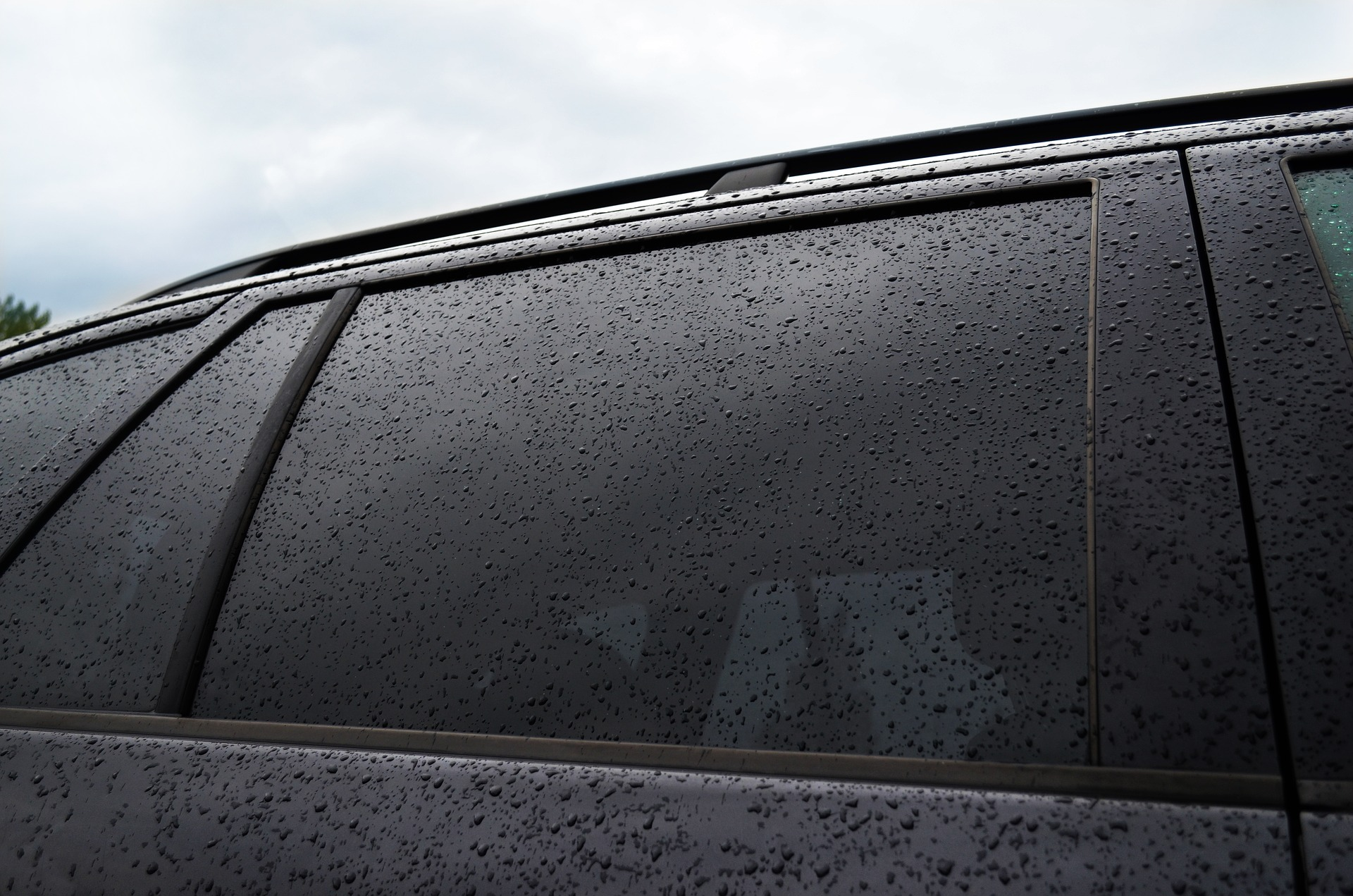 dark window tint on a wet car