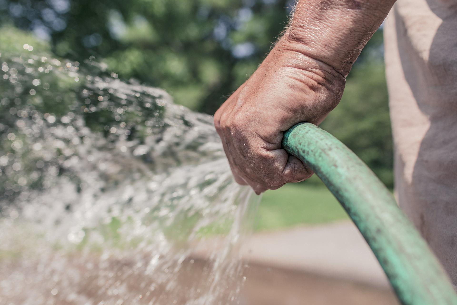 holding a spraying green hose